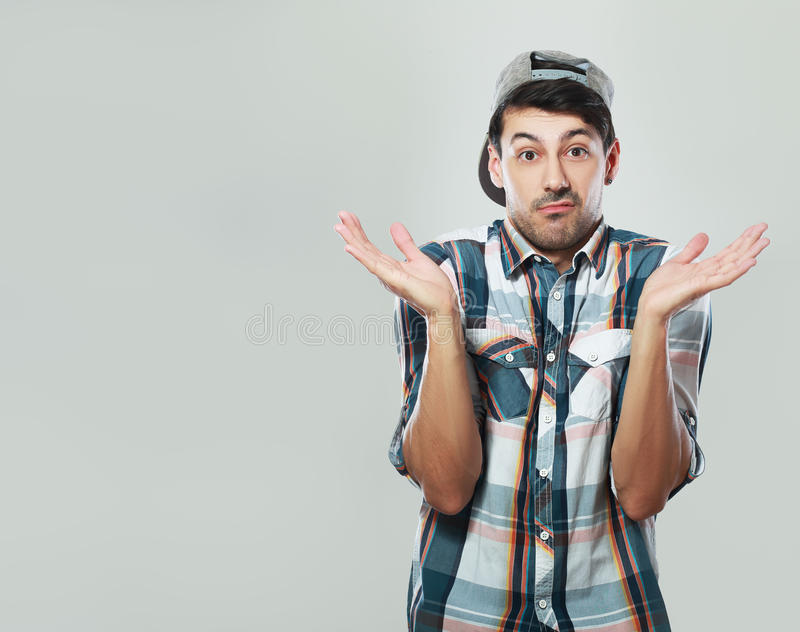 Man shrugging. Young man in shirt and cap shrugging over grey background royalty free stock photography