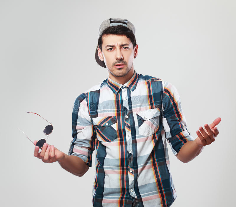 Man shrugging. Young man in shirt and cap shrugging over grey background stock photography