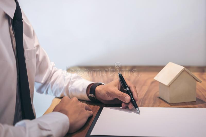 Man sign a home insurance policy on home loans. Businessman signing contract insurance royalty free stock image