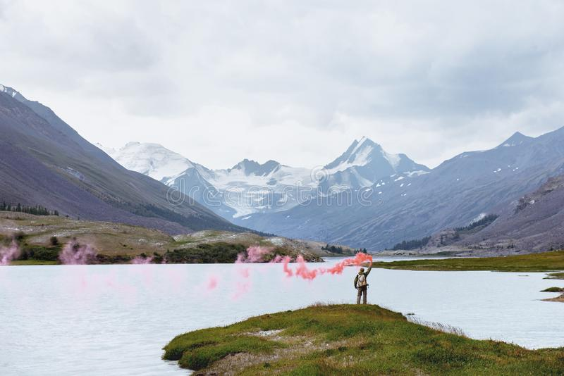 Man with signal fire on background of mountain lake. Man stands with red signal fire on background of beautiful mountain lake and glacier royalty free stock photography