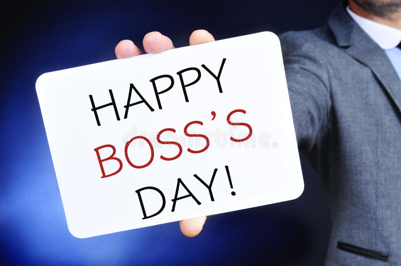 Man with a signboard with the text happy boss day. A young caucasian businessman shows a signboard with the text happy boss day written in it stock photos