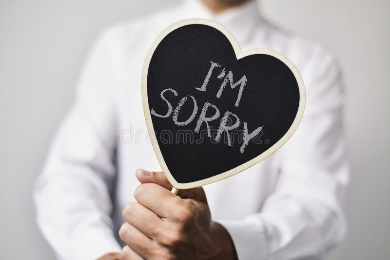 Man with a signboard with the text I am sorry. A young caucasian man wearing a white shirt shows a heart-shaped signboard with the text I am sorry written in it stock photos