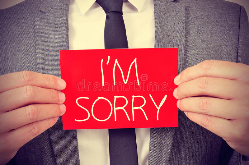 Man with signboard with the text I am sorry. A young man showing a red signboard with the text I am sorry written in it stock image