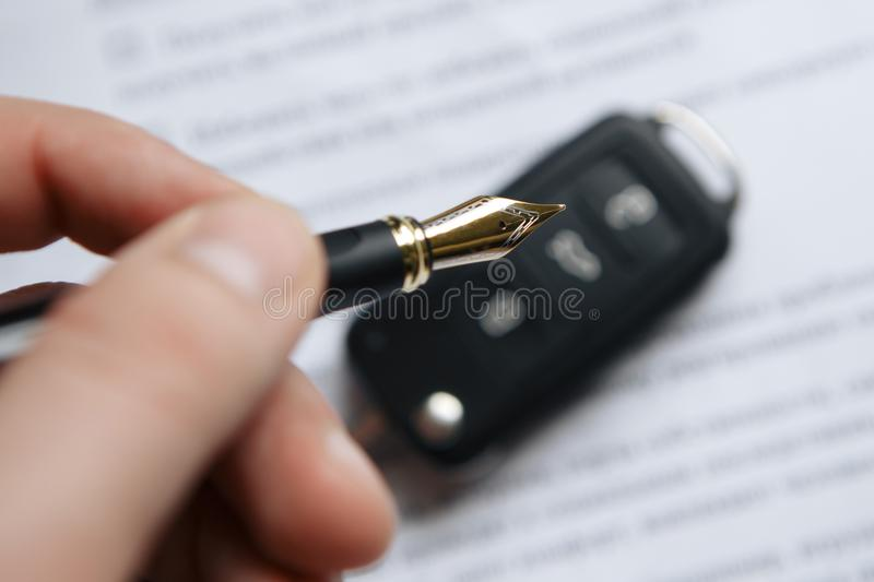 Man signing car insurance document or lease paper. Writing signature on contract or agreement. Buying or selling new or stock photography