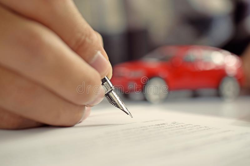Man signing car insurance document. Writing signature on contract or agreement. Buying or selling new or used vehicle. Man signing car insurance document royalty free stock photos