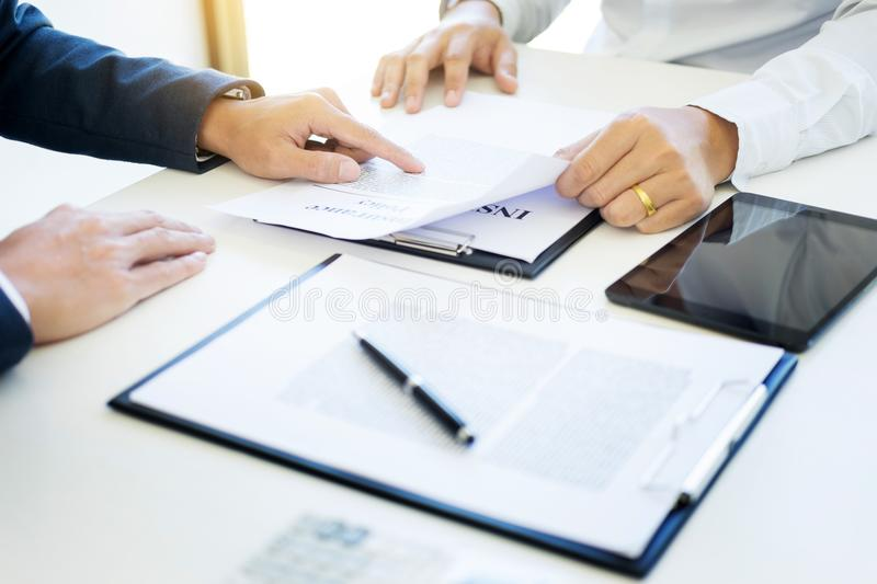 Man signing a car insurance policy, the agent is holding the doc. Ument royalty free stock images
