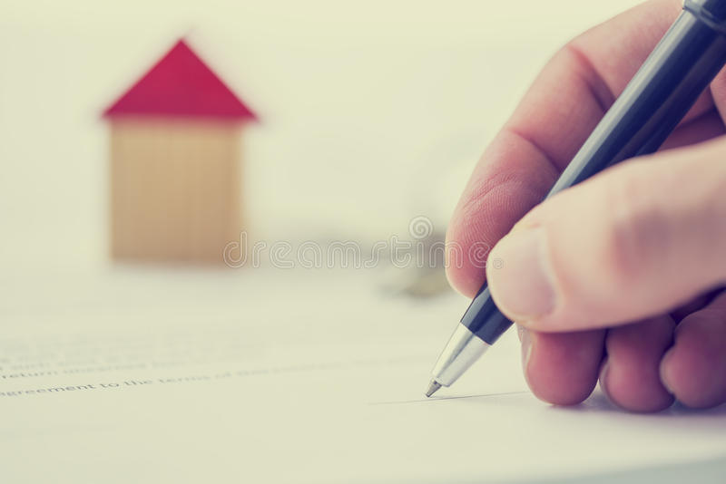Man signing a deed of sale on a house. Retro image of a man signing a deed of sale, mortgage document or insurance contract on a house with a closeup view of his stock image