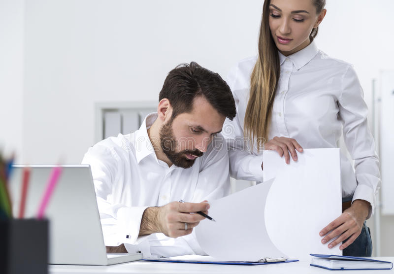 Man signing documents given by secretary stock photos