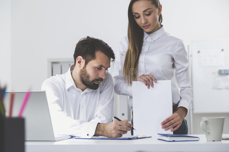 Man signing documents given by woman royalty free stock photo