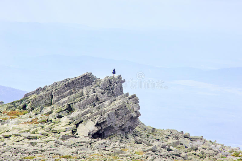 Man silhouette with backpack stay on rock peak from rectangular blocks royalty free stock image