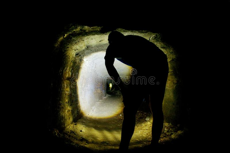 Man silhouette in a cave or dry sandstone water channel, back shot. Visiting of old underground stock photo