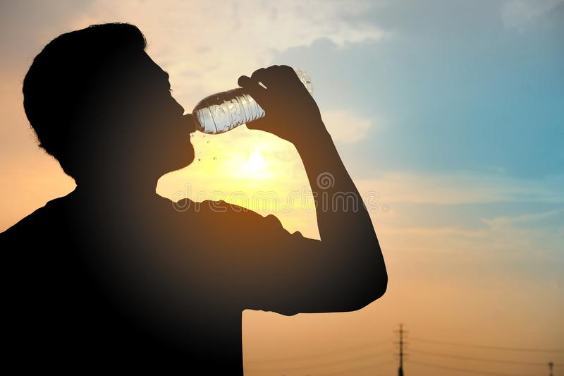 Man silhouette is drinking fresh water. On the background of the sunset sky stock photo