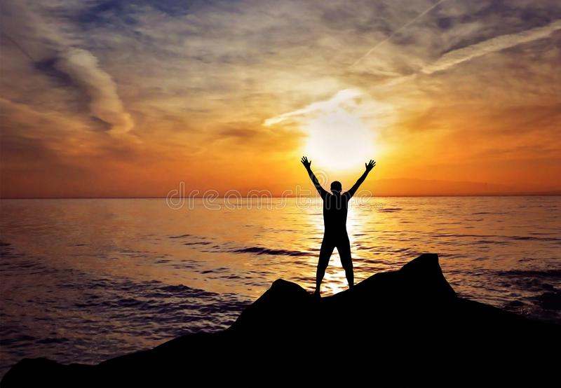 Man silhouette hands up in the air freedom success stock photo