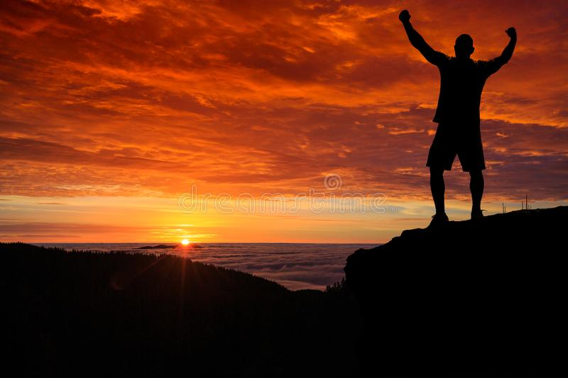 Man silhouette on the mountain top watching the sunrise over clouds and forest royalty free stock photos