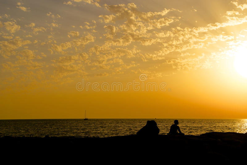Man silhouette on reef at sunset royalty free stock photos