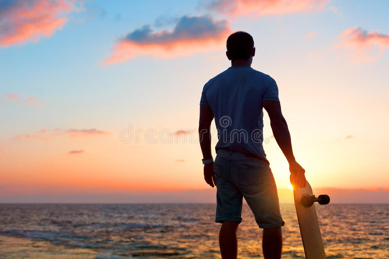 Man silhouette with skateboard near the ocean stock photo