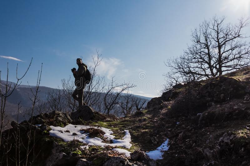 Man silhouette stay on sharp rock peak. Satisfy hiker enjoy view royalty free stock images