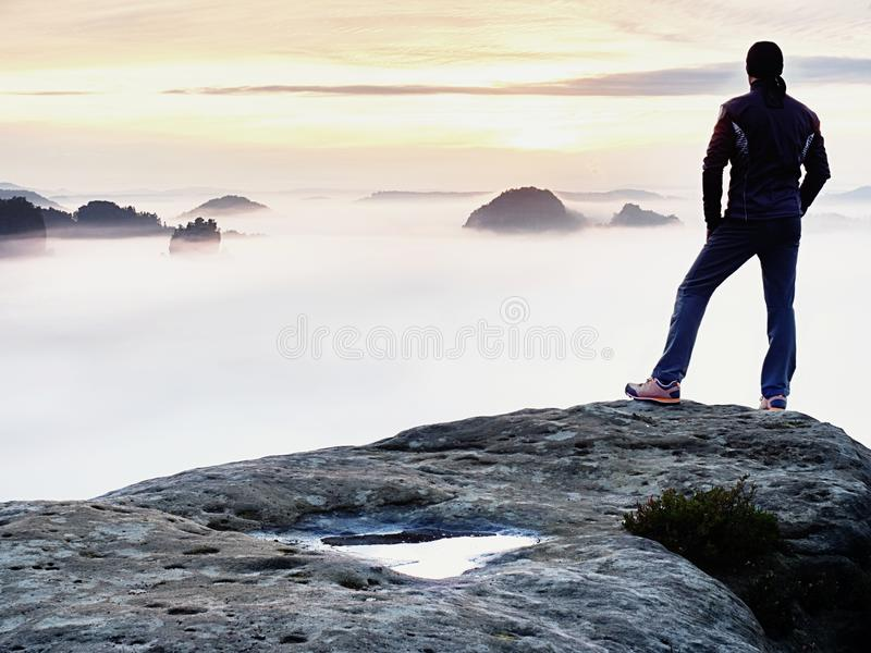 Man silhouette stay on sharp rock peak. Satisfy hiker enjoy view. Tall man on rocky cliff royalty free stock images