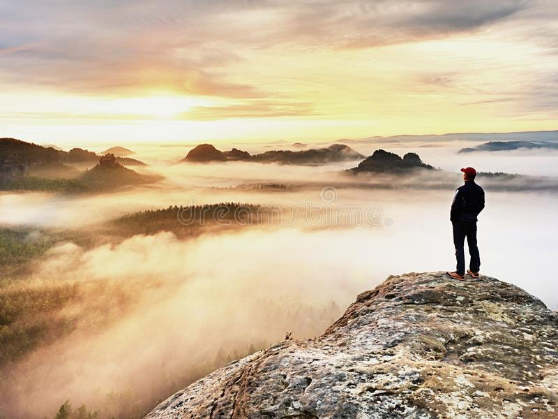 Man silhouette stay on sharp rock peak. Satisfy hiker enjoy view. Tall man on rocky cliff royalty free stock image