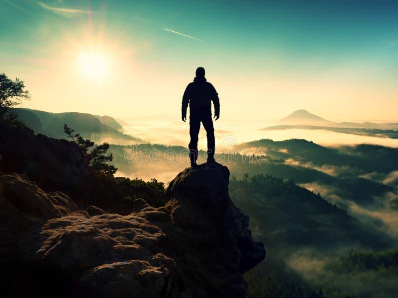 Man silhouette stay on sharp rock peak. Satisfy hiker enjoy view. royalty free stock photo