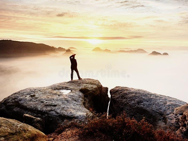 Man silhouette stay on sharp rock peak. Satisfy hiker enjoy view. Tall man on rocky cliff royalty free stock photo