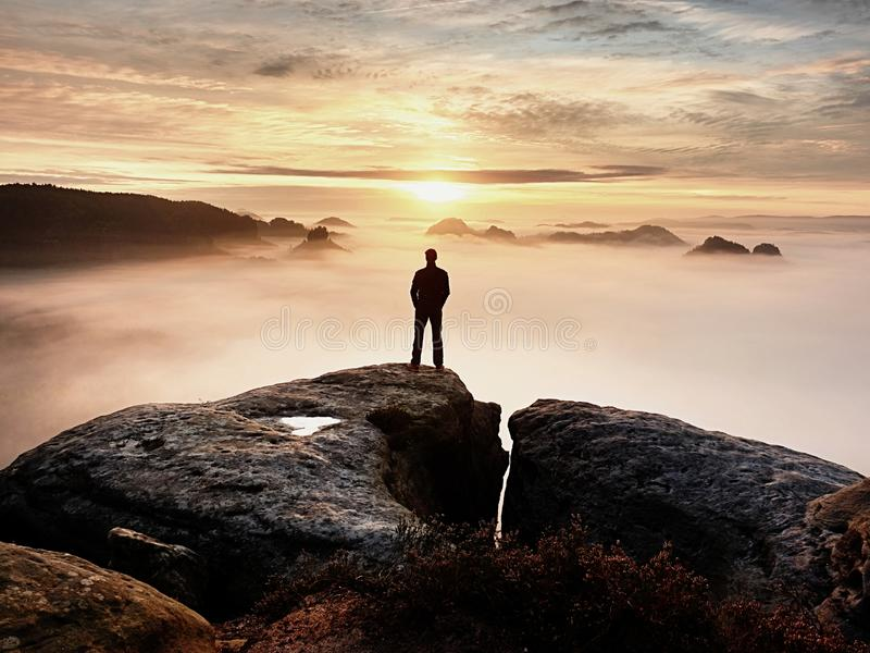 Man silhouette stay on sharp rock peak. Satisfy hiker enjoy view. Tall man on rocky cliff royalty free stock photography