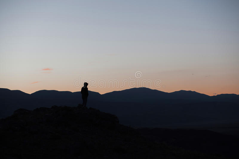 Man silhouette stay on sharp rock peak. Satisfy hiker enjoy view. Tall man on rocky cliff watching down to landscape. royalty free stock images
