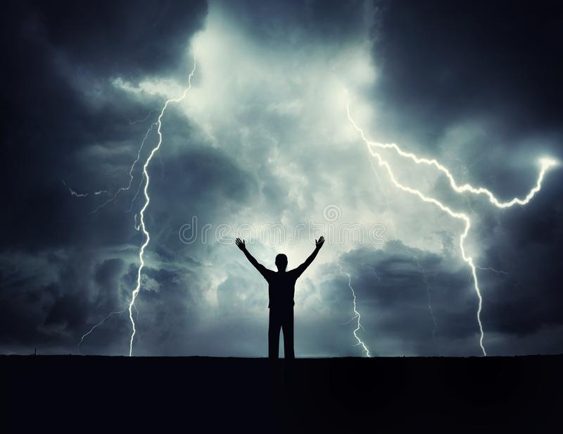 Man silhouette on a storm background. Lord of the lightning. stock photos