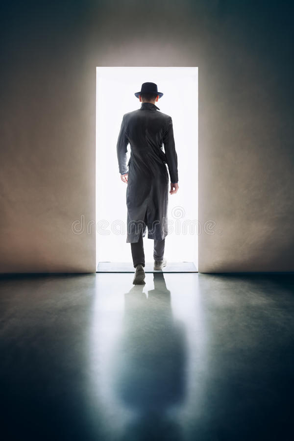 Man silhouette walking away in the light of opening door in dark royalty free stock images