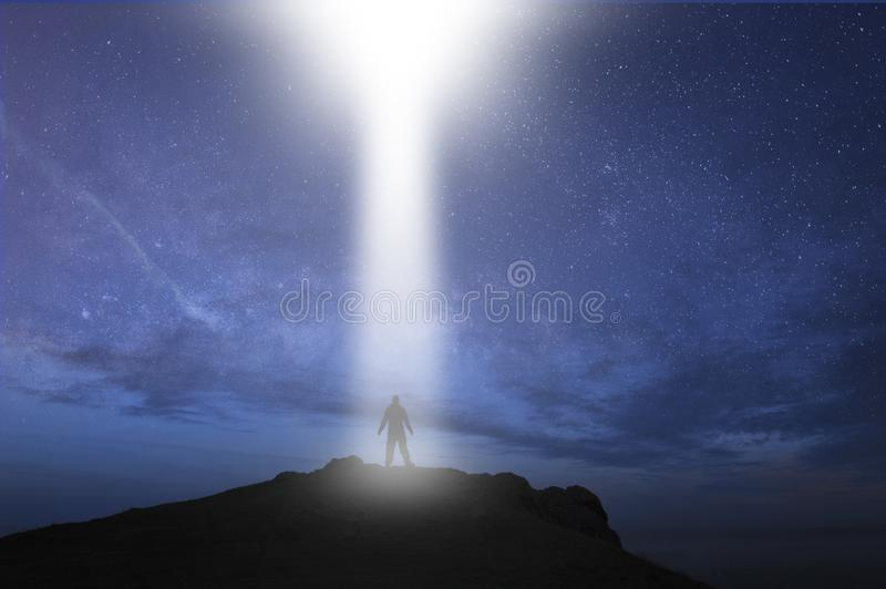 A man silhouetted, standing on top of a hill with a UFO light beam coming down at night.  vector illustration