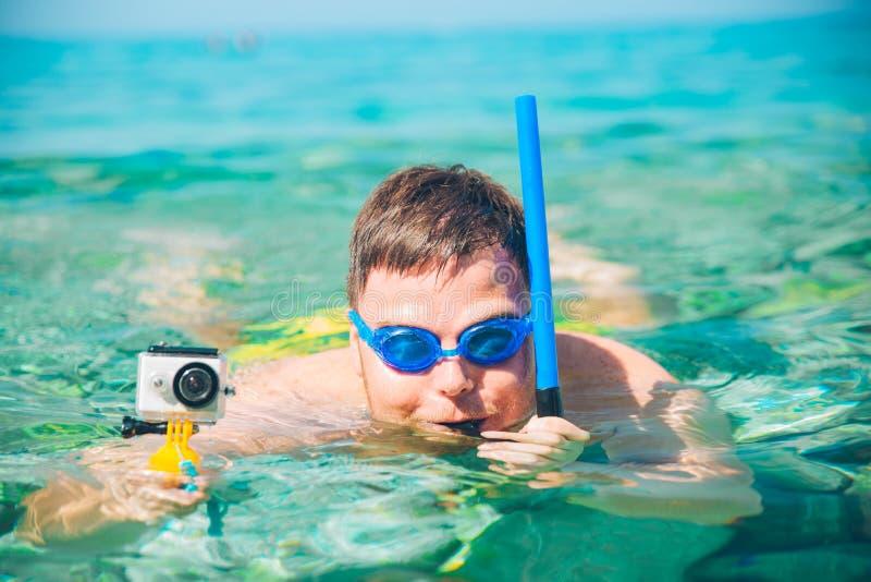 Man simning under vatten med maskeringen och åtgärda kameran royaltyfri fotografi