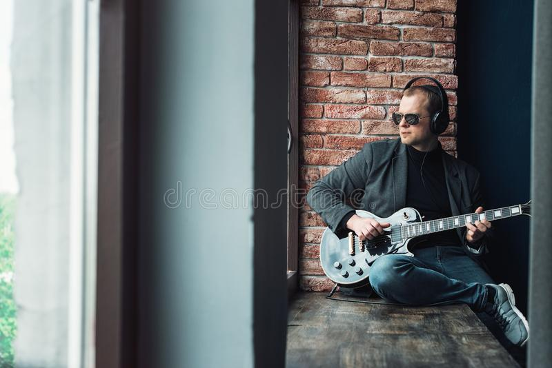 Man singer sitting on a window sill in a headphones with a guitar recording a track in a home studio royalty free stock photography