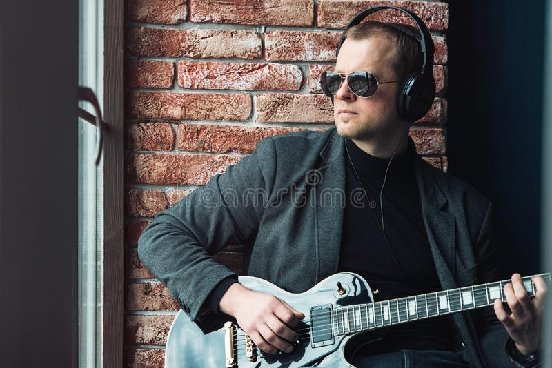 Man singer sitting on a window sill in a headphones with a guitar recording a track in a home studio royalty free stock image