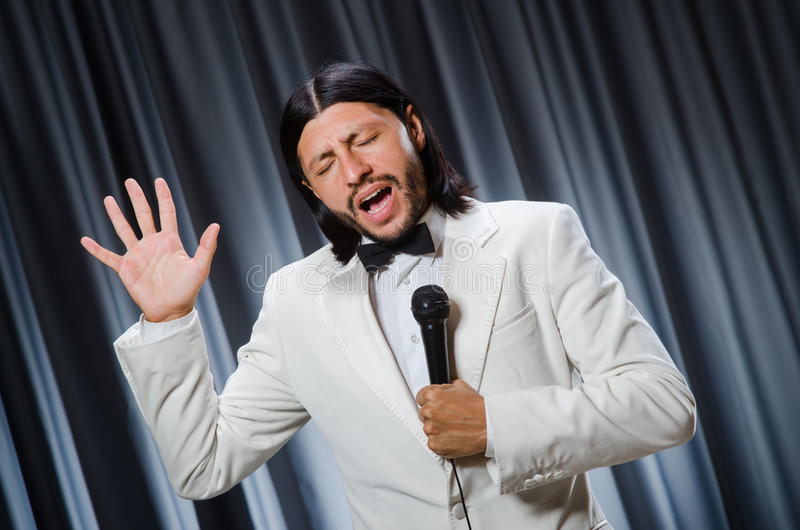 Man singing in front of curtain. In karaoke concept stock image