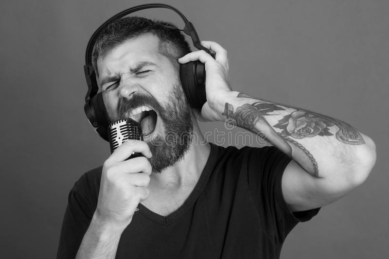 Man sings on green background. Singer with beard and excited face listens to music. Relax and music concept. Dj with beard wears headphones stock photo