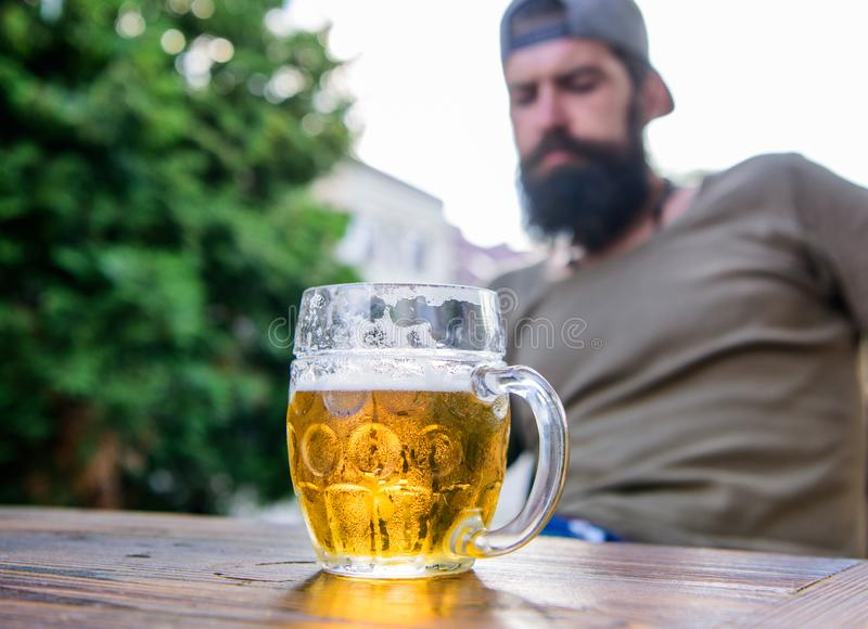 Man sit cafe terrace enjoying beer defocused. Craft beer is young, urban and fashionable. Distinct beer culture. Mug. Cold fresh beer on table close up stock photography