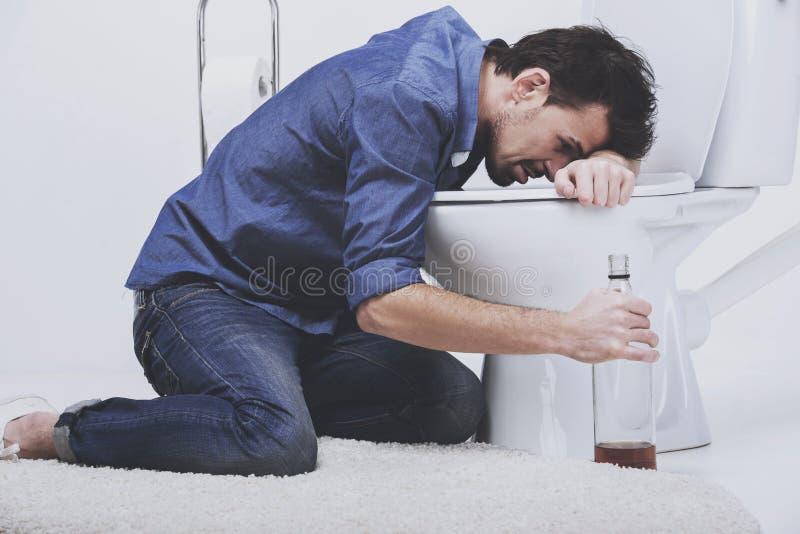 Man sit near toilet with bottle. stock photo