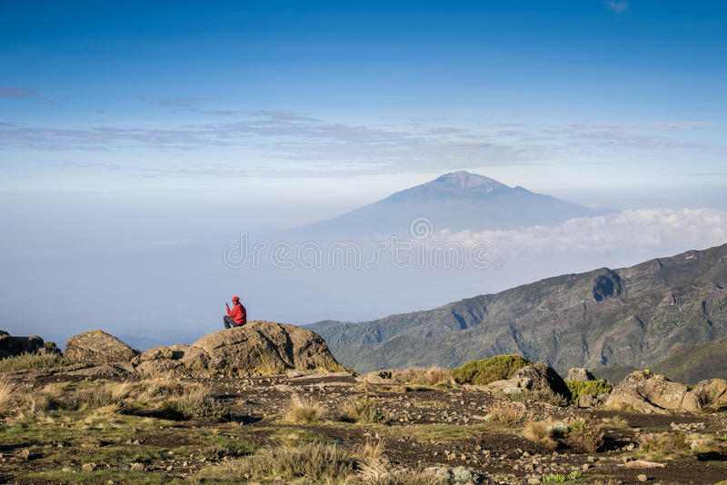 Man siting with his phone in the mountains royalty free stock photography