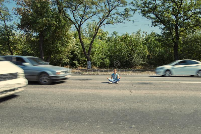 A man sits on an asphalt road and meditates past passing cars.  stock images