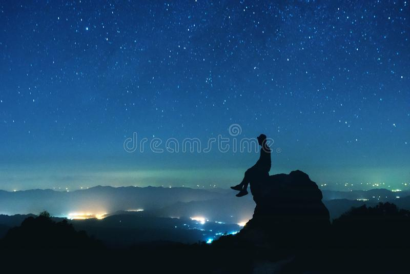 Man sits on big rock on night sky background stock images