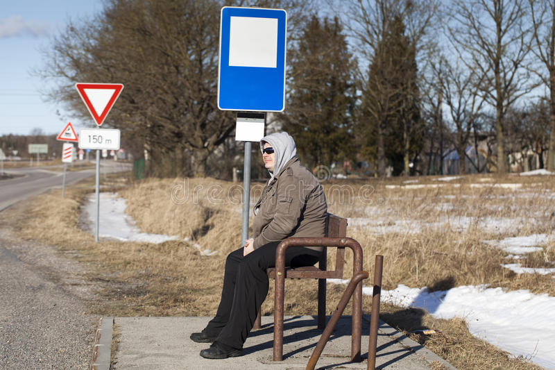 Man sits at a bus stop. In the countryside royalty free stock photos