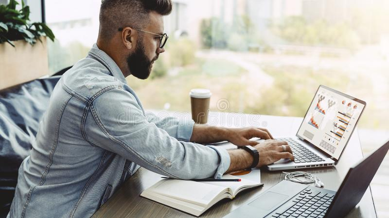 Man sits in cafe, works on laptop with charts, graphs on screen. Businessman is planning business.Online marketing. Hipster man sits in cafe, works on laptop stock photo