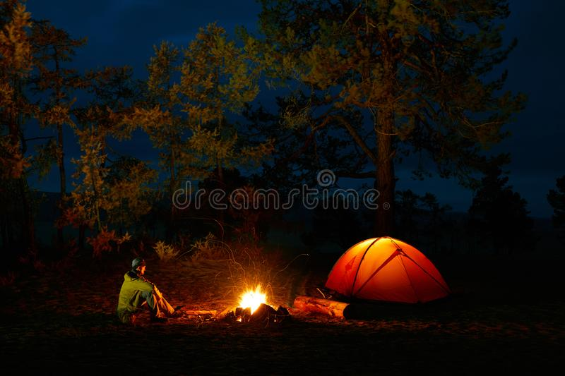 A man sits by the fire near a tent on the shore of Lake Baikal royalty free stock images