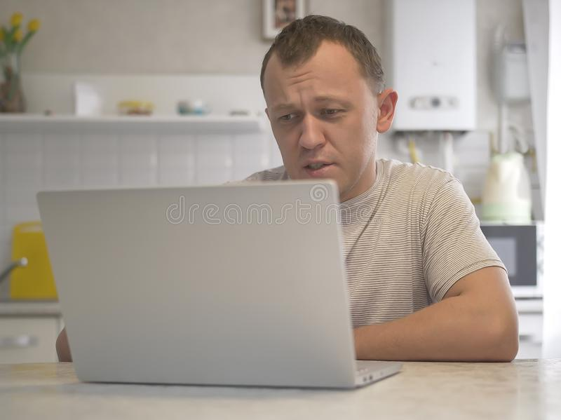 A young man sits in his kitchen with a laptop. stock images