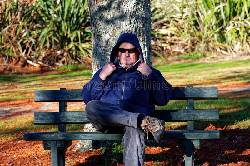 A man sits with is hood up on a seat in the park stock photo