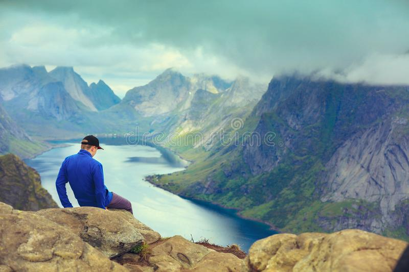 A man sits on the cliff edge. A man sits on the mountain`s cliff edge. Beautiful mountain landscape. Nature Norway, Lofoten islands royalty free stock images