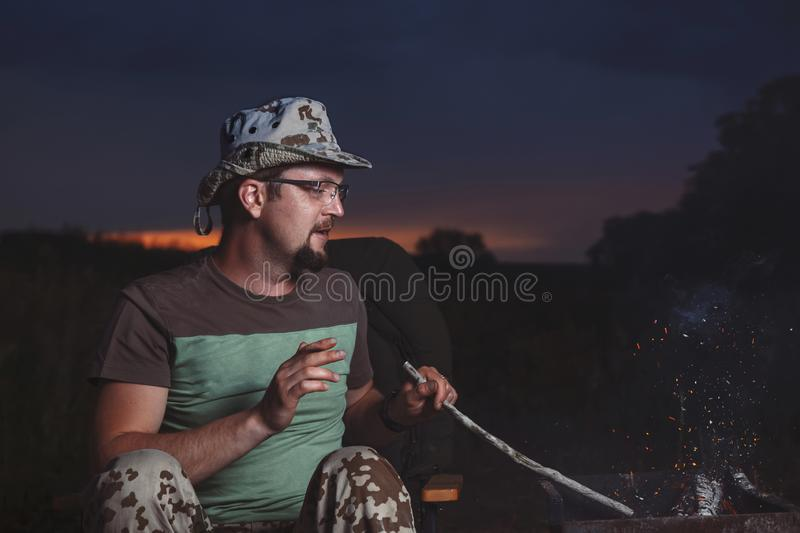 Man sits at night around the fire from which sparks fly, in the summer under the open sky.  stock photography