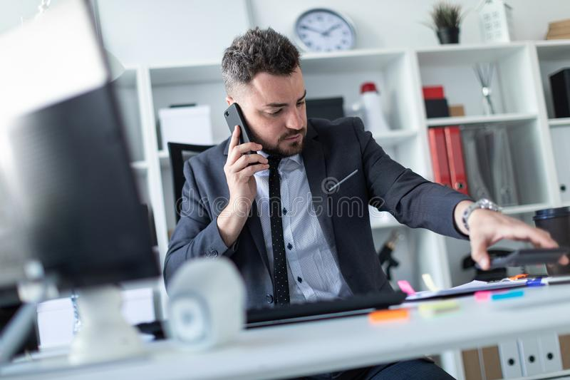 A man sits in the office at the desk, talks on the phone, works with documents and puts aside the calculator. royalty free stock image