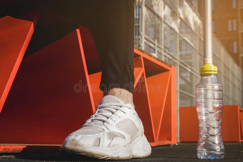 A man sits on an orange bench in black pants and white sneakers on the sports field stock photography