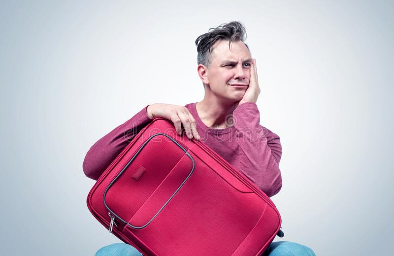 Man sits with a red suitcase waiting for a trip. Expectation concept.  stock photo